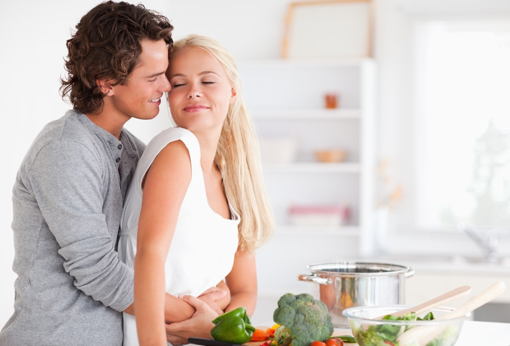 Couple hugging while cooking