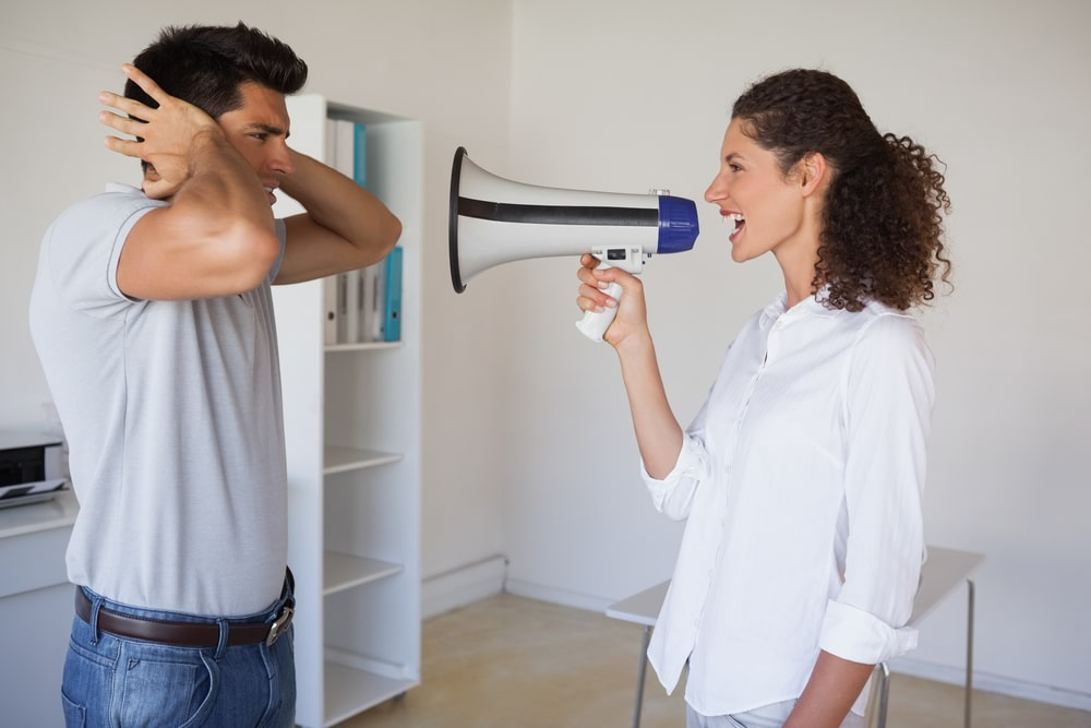 Woman nagging while man covering ears