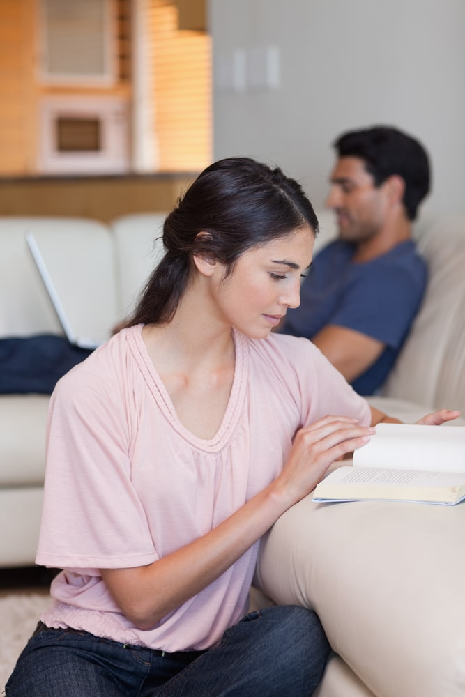 Woman reading book while husband using laptop