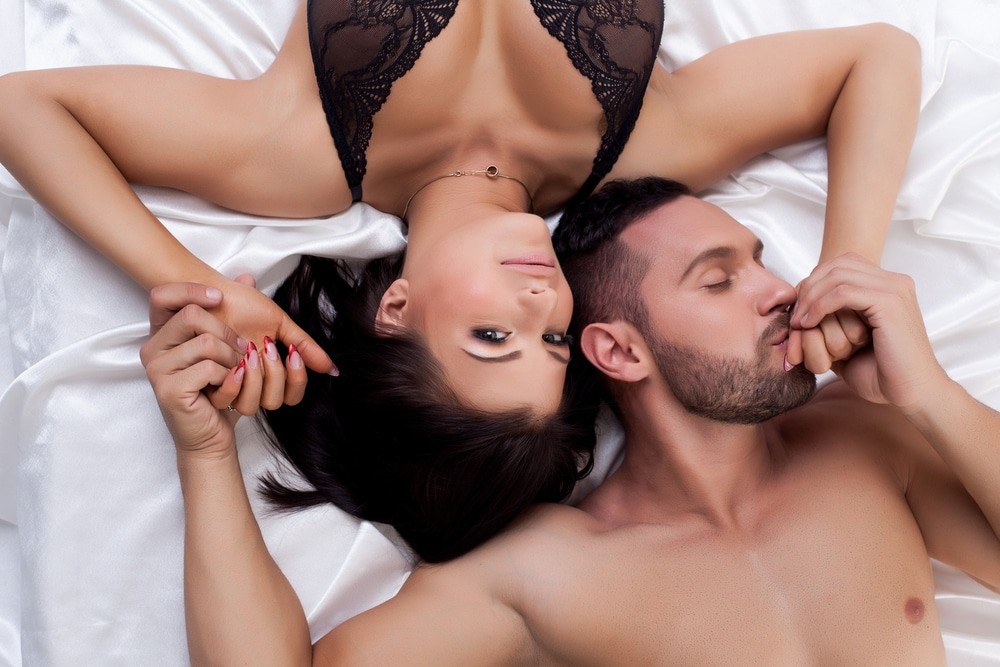 Couple lying in satin bed sheet